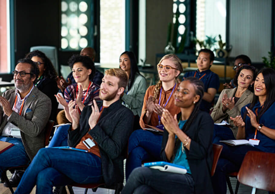 A diverse group seated at a conference applauding