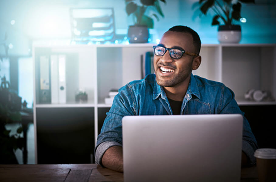 A smiling black male grad student on his laptop