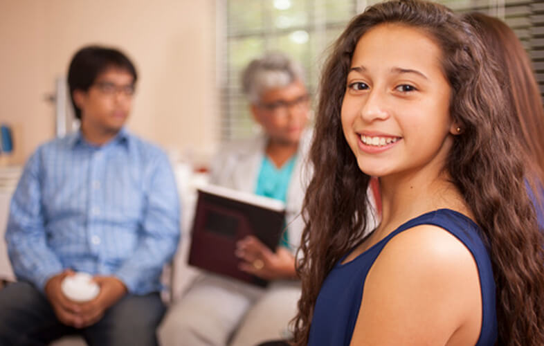 A young teen girl smiling and facing the camera in a therapy group therapy session. Several other participants are obscured in the background.