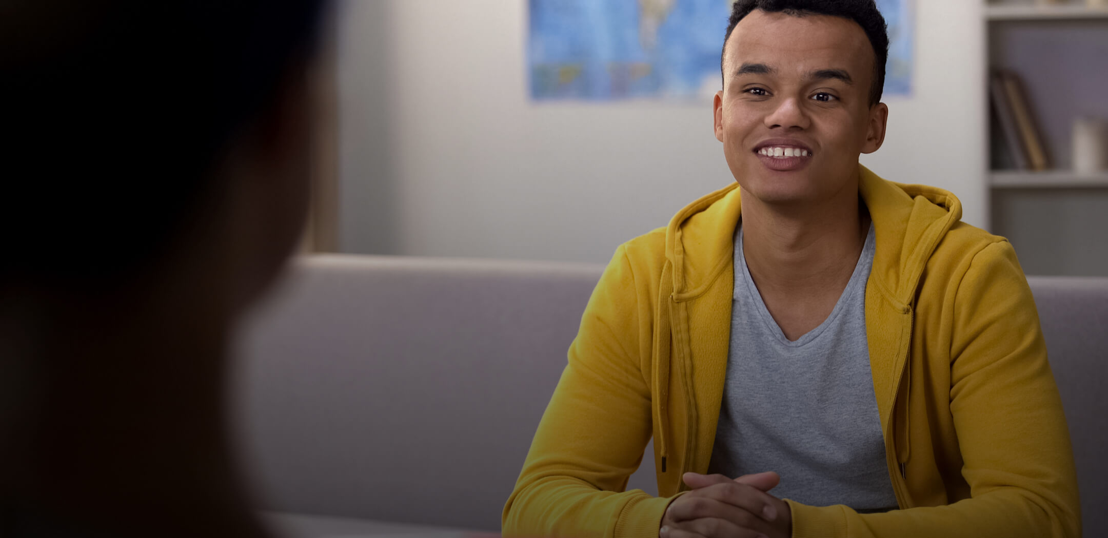 A bi-racial youth in a yellow hoodie smiling and seated in front of a therapist