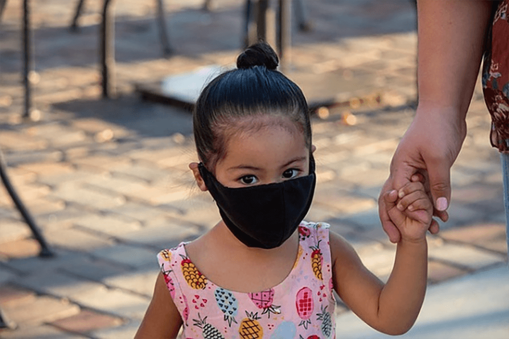 Young child with face mask holding caregiver's hand
