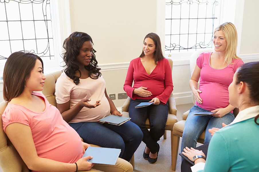 A diverse group of pregnant women sitting in a circle for a prenatal workshop with a nurse