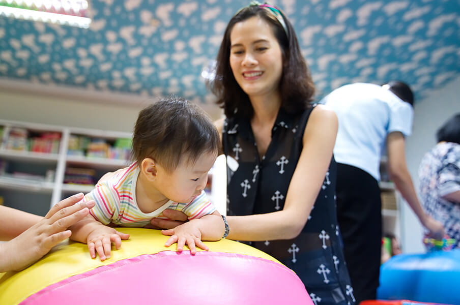 An Asian mom holding her toddler on a large rubber ball at a family play and learning centre