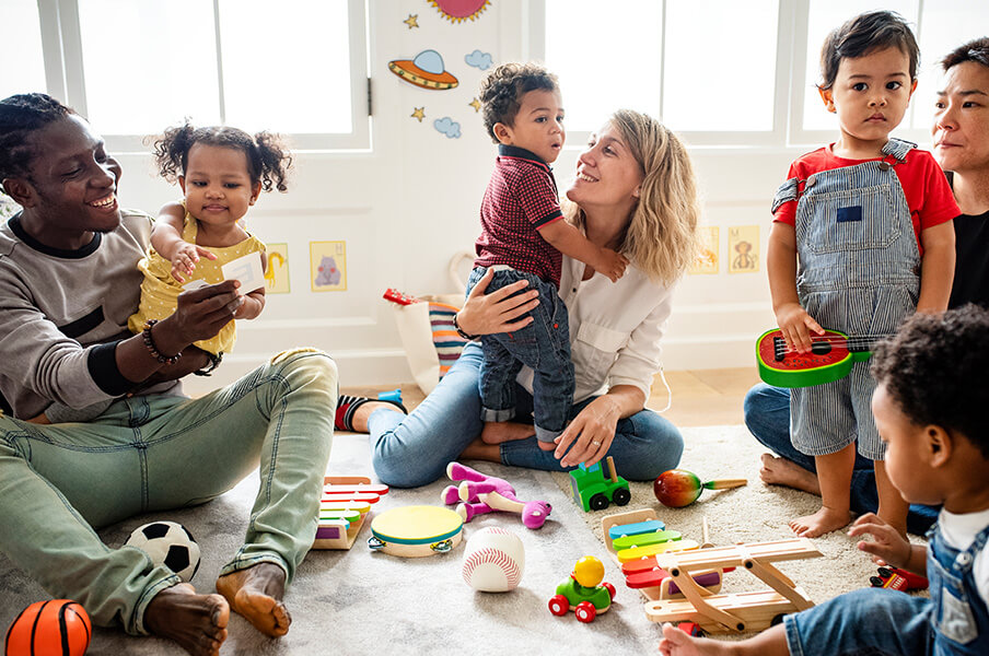 A diverse group of parents including a dad and several moms with their toddlers at a play centre