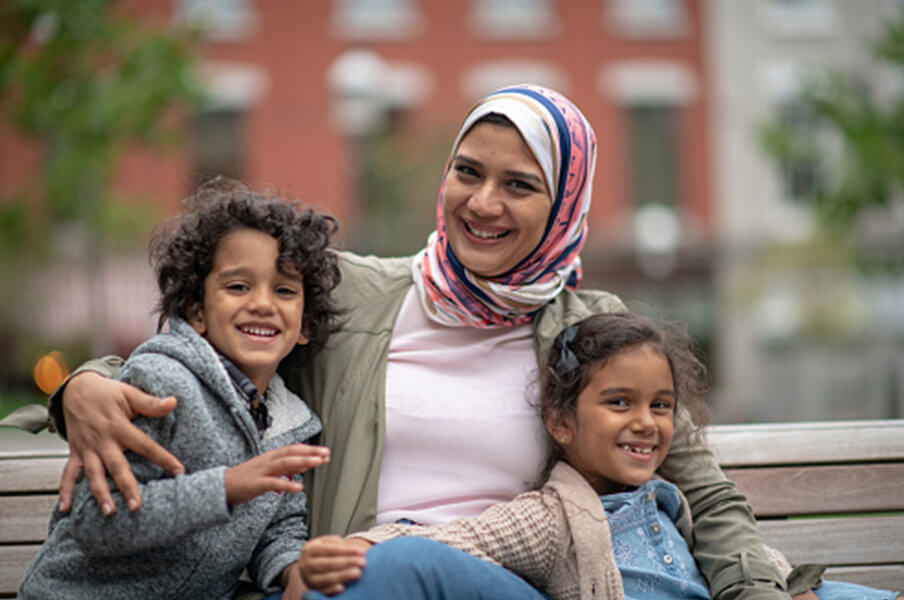 A smiling mother, daughter and son of middle-eastern descent, sitting on a park bench