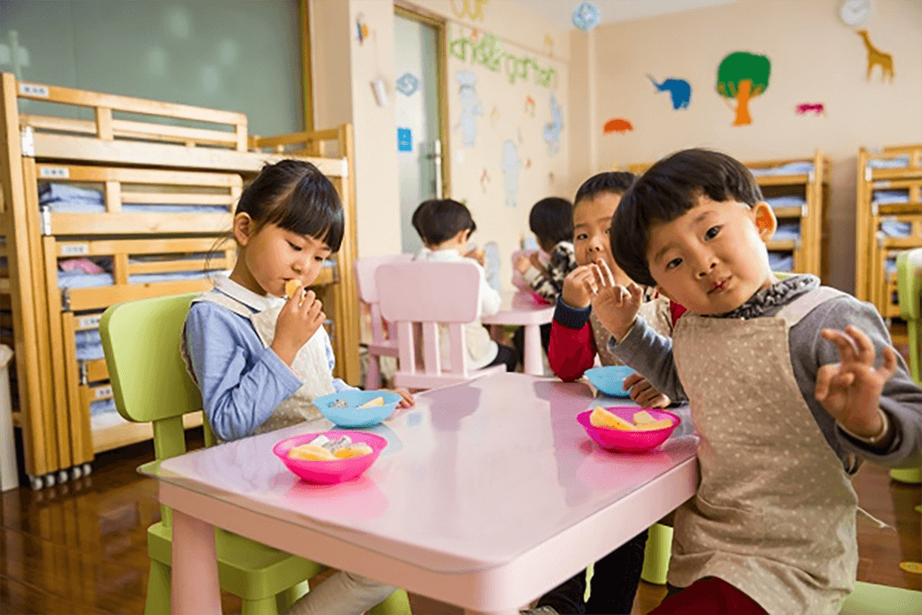Asian kindergarten children at a table eating a snack