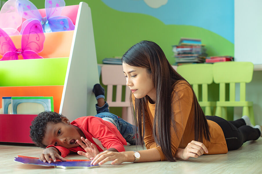 A child therapist works with a young child with behavioural issues in a brightly coloured room