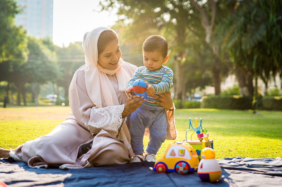 Woman of S. Asian descent holding her toddler who is playing with toys in the park