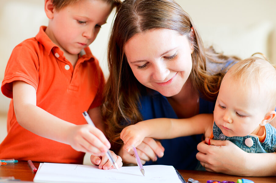 Mom watching child and infant draw in a book