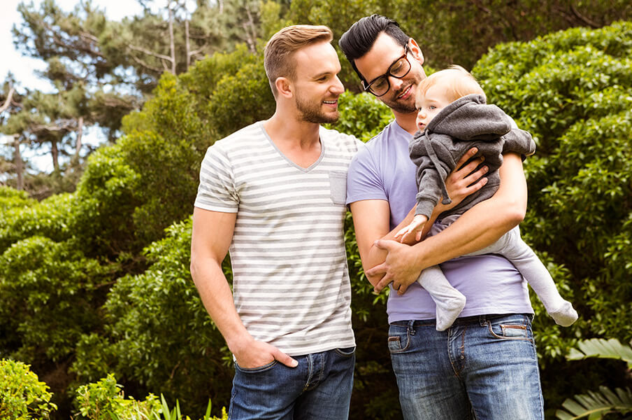 2 gay fathers holding their toddler