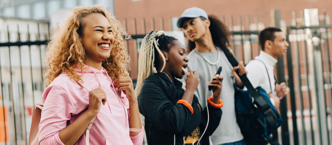 Group of four diverse youth of colour walking in a school yard