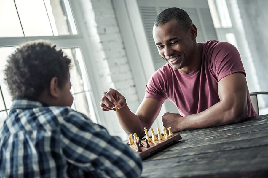 A young teen of colour is playing chess with a Youth worker/mentor