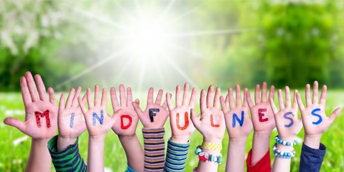 Using mindfulness to support the grief process image showing kids hands with letters spelling mindfulness