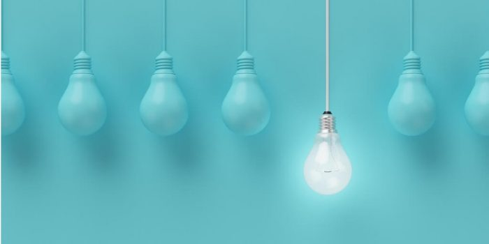 Leadership and motivation image of a row of lightbulbs with one shinning