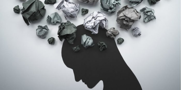person silhouette with crumpled papers representing anxiety