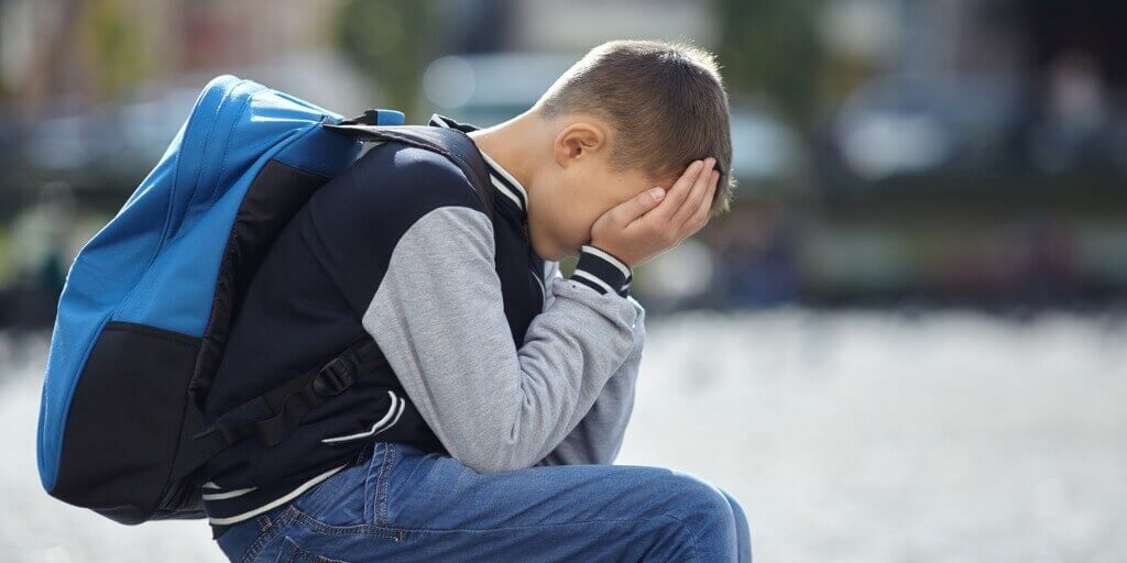 anxious child showing signs of school refusal